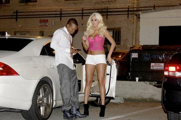 **EXCLUSIVE** Playmate Karissa Shannon - in barely there white shorts - caresses boyfriend Sam Jones III before getting into their white Mercedes outside of Eden nightclub