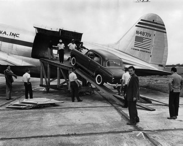Der erste auf dem Luftwege Colon nach Guatemala beförderte Mercedes-Benz Typ 220 a wird auf dem Flughafen Aurora aus einem Lufttransporter der Aero vias Sud Americana, Inc. entladen, 1955.