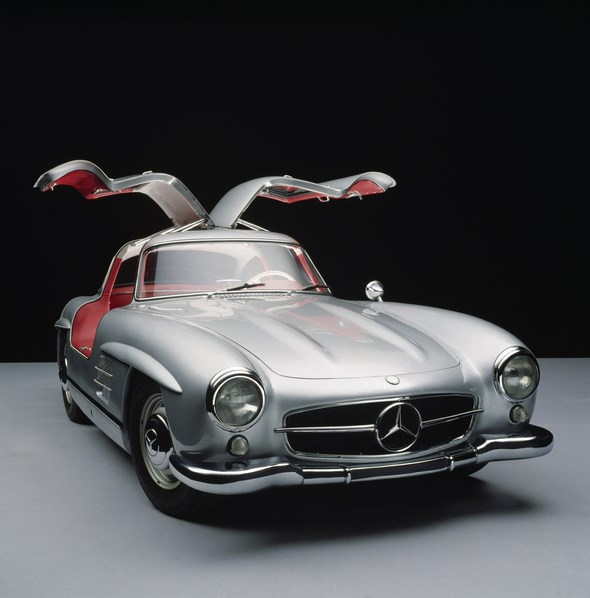 """Der oft als Design-Ikone bezeichnete Mercedes-Benz 300 SL """"Flügeltürer"""" verkörperte nach dem Zweiten Weltkrieg Rasse und Klasse wie kein anderes Auto seiner Zeit. Er ist bis heute ein hoch begehrter Traumwagen und wurde 1999 von einer internationalen Jury von Automobilexperten zum """"Sportwagen des Jahrhunderts"""" gewählt. Der von Friedrich Geiger gestaltete 300 SL fasziniert seit seinem Debüt Im Jahr 1954 nicht nur mit den konstruktiv bedingten Flügeltüren, sondern trägt auch als erstes Mercedes-Benz Straßenfahrzeug keinen senkrecht stehenden Kühlergrill. Stattdessen schmückt ihn eine waagerechte Lufteinlassöffnung mit dem Stern in der Mitte - ein Gestaltungselement, das bis heute zahlreiche Mercedes-Benz Baureihen prägt."""