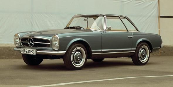 """Der Mercedes-Benz 230 SL erscheint 1963 mit ungewohnten neuen Proportionen und Linien – und dem unverwechselbaren """"Pagodendach"""". Das abnehmbare Hardtop sieht nicht nur gut aus, seine spezielle Form mit leicht abgesenktem Mittelteil erhöht auch die Dachsteifigkeit und damit die Sicherheit. Zu den praktischen Vorteilen zählt auch die leichtere und stabilere Montagemöglichkeit eines Dachträgers, beispielsweise zum Transport von Skiern. Die vertikalen Hauptscheinwerfer hat Mercedes-Benz bereits 1957 beim 300 SL Roadster eingeführt und in weiteren Modellen fortgesetzt. Sie dienen als typisches Marken-Erkennungszeichen in der Frontansicht."""